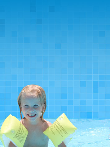 Little boy in an above ground pool with floaties The Recreational Warehouse Southwest Florida's Leading Warehouse for Spas, Hot Tubs, Pool Heaters, Pool Supplies, Outdoor Kitchens and more!