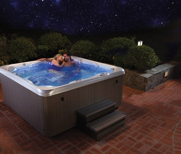 Couple cuddling in their Rhythm Hot Tub Spa | Hot Springs Spas available at the Recreational Warehouse Southwest Florida (Naples, Fort Myers and Port Charlotte Locations) Pool Warehouse