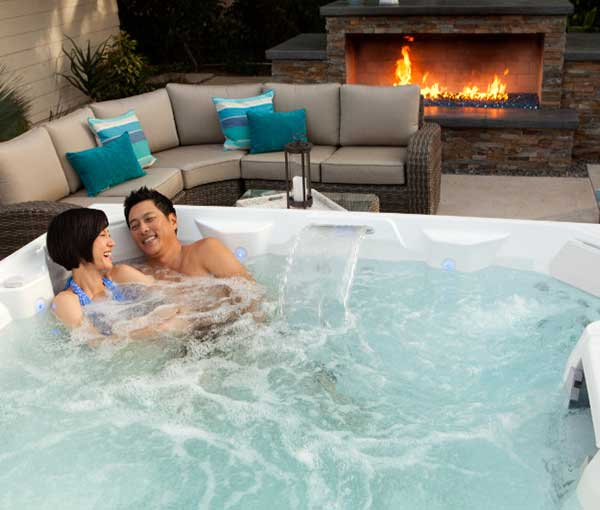 Couple cuddling together in their Pulse Hot Tub Spa | Hot Springs Spas available at the Recreational Warehouse Southwest Florida (Naples, Fort Myers and Port Charlotte Locations) Pool Warehouse