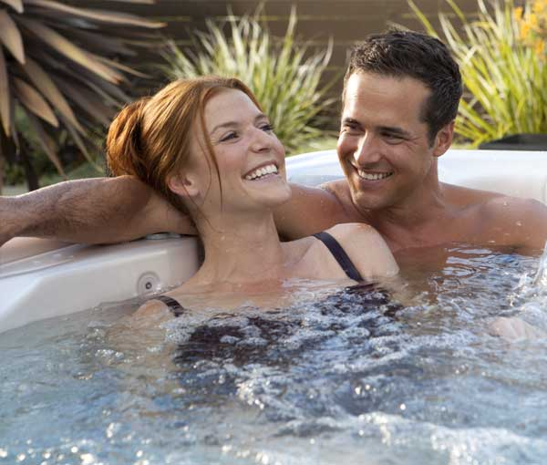 Couple cuddling together in their Relay Hot Tub Spa | Hot Springs Spas available at the Recreational Warehouse Southwest Florida (Naples, Fort Myers and Port Charlotte Locations) Pool Warehouse