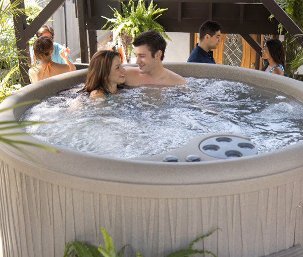 Couple enjoying Aptos Hot Tub Spa | Freeflow Spas available at the Recreational Warehouse Southwest Florida (Naples, Fort Myers and Port Charlotte Locations) Pool Warehouse