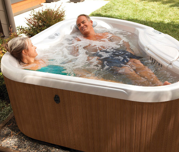 Couple enjoying quality time in their TX Hot Tub Spa | Hot Springs Spas available at the Recreational Warehouse Southwest Florida (Naples, Fort Myers and Port Charlotte Locations) Pool Warehouse