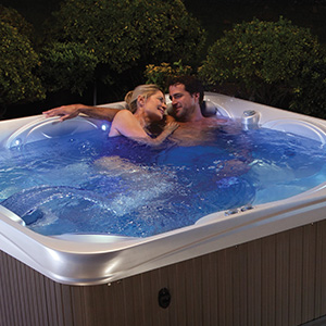 Couple relaxing in a hot tub from The Recreational Warehouse Southwest Florida's Leading Warehouse for Spas, Hot Tubs, Pool Heaters, Pool Supplies, Outdoor Kitchens and more!