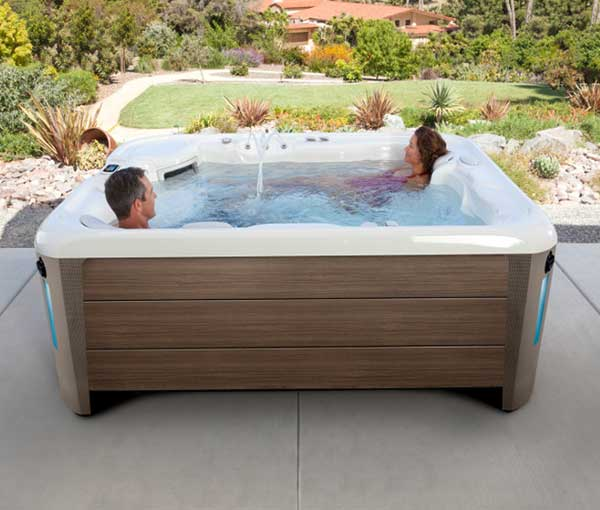 Couple lounging in Sovereign Hot Tub Spa | Hot Springs Spas available at the Recreational Warehouse Southwest Florida (Naples, Fort Myers and Port Charlotte Locations) Pool Warehouse