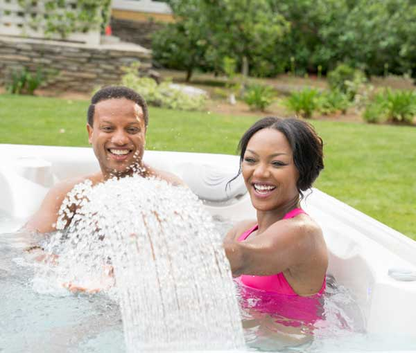 Couple playing with waterfall in Vanto Hot Tub Caldera Spa | Caldera Spas available at the Recreational Warehouse Southwest Florida (Naples, Fort Myers and Port Charlotte Locations) Pool Warehouse