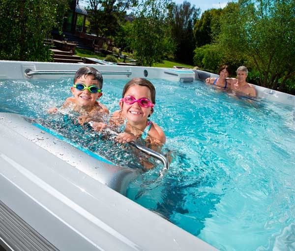 Couple relaxing and children using kickbar on E500 Endless Pool | Endless Pools Fitness Systems available at the Recreational Warehouse Southwest Florida (Naples, Fort Myers and Port Charlotte Locations) Pool Warehouse