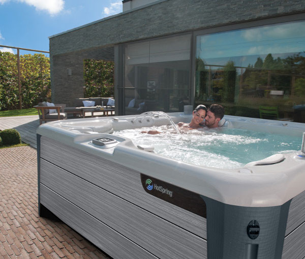 Couple relaxing in their Envoy Hot Tub Spa | Hot Springs Spas available at the Recreational Warehouse Southwest Florida (Naples, Fort Myers and Port Charlotte Locations) Pool Warehouse