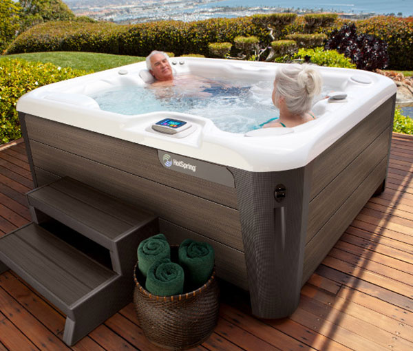 Couple lounging in their Jetsetter LX Hot Tub Spa | Hot Springs Spas available at the Recreational Warehouse Southwest Florida (Naples, Fort Myers and Port Charlotte Locations) Pool Warehouse
