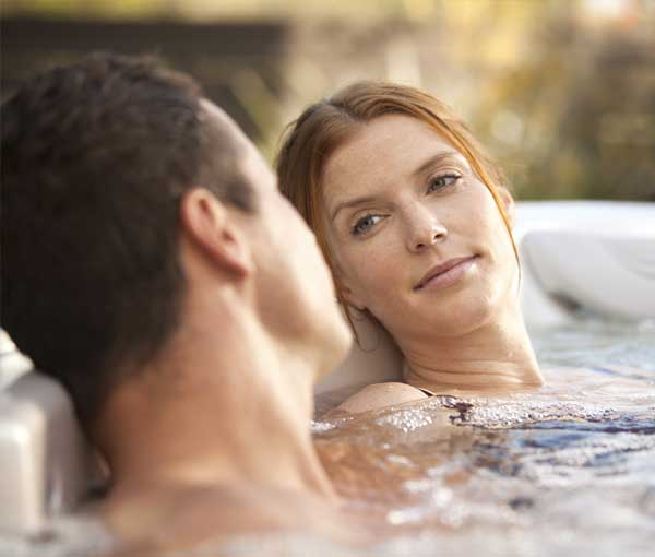 Couple relaxing together in their Relay Hot Tub Spa | Hot Springs Spas available at the Recreational Warehouse Southwest Florida (Naples, Fort Myers and Port Charlotte Locations) Pool Warehouse