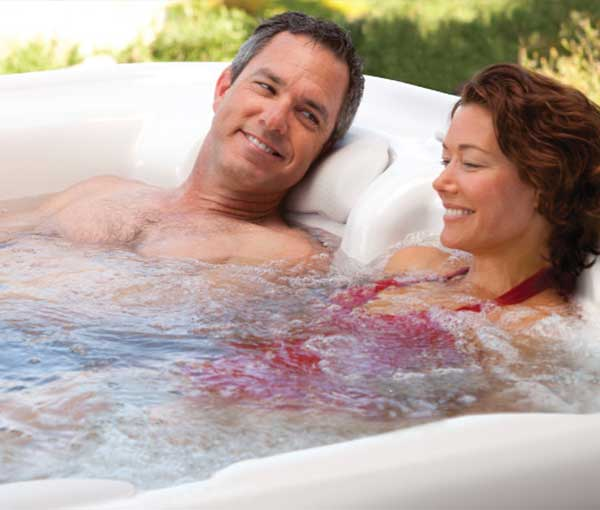 Couple relaxing in Sovereign Hot Tub Spa | Hot Springs Spas available at the Recreational Warehouse Southwest Florida (Naples, Fort Myers and Port Charlotte Locations) Pool Warehouse