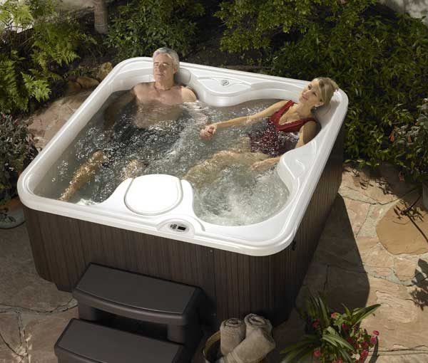 Couple lounging and relaxing in their SX Hot Tub Spa | Hot Springs Spas available at the Recreational Warehouse Southwest Florida (Naples, Fort Myers and Port Charlotte Locations) Pool Warehouse