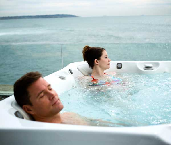 Couple relaxing in Tahitian Hot Tub | Caldera Spas available at the Recreational Warehouse Southwest Florida (Naples, Fort Myers and Port Charlotte Locations) Pool Warehouse