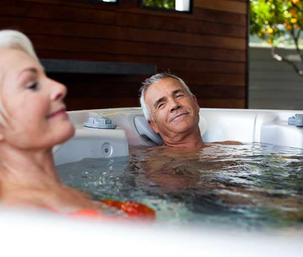 Couple relaxing in Tarino Hot Tub Caldera Spa | Caldera Spas available at the Recreational Warehouse Southwest Florida (Naples, Fort Myers and Port Charlotte Locations) Pool Warehouse