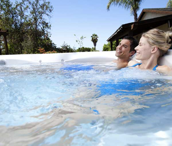Couple relaxing in Tempo Hot Tub Spa with Accessories | Hot Springs Spas available at the Recreational Warehouse Southwest Florida (Naples, Fort Myers and Port Charlotte Locations) Pool Warehouse