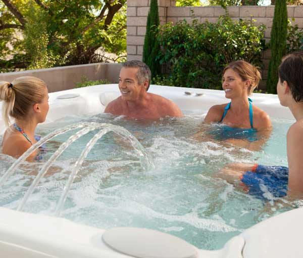 Family enjoying their Grandee Hot Tub Spa | Hot Springs Spas available at the Recreational Warehouse Southwest Florida (Naples, Fort Myers and Port Charlotte Locations) Pool Warehouse