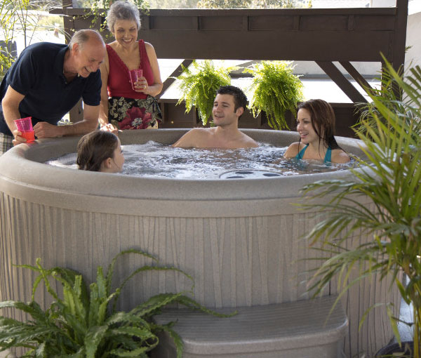 Family gathering around Aptos Hot Tub Spa | Freeflow Spas available at the Recreational Warehouse Southwest Florida (Naples, Fort Myers and Port Charlotte Locations) Pool Warehouse