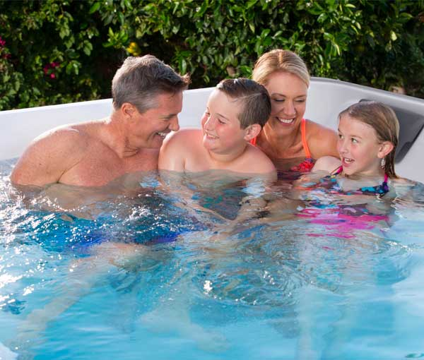 Family lounging in R200 Endless Pool   Endless Pools Fitness Systems available at the Recreational Warehouse Southwest Florida (Naples, Fort Myers and Port Charlotte Locations) Pool Warehouse