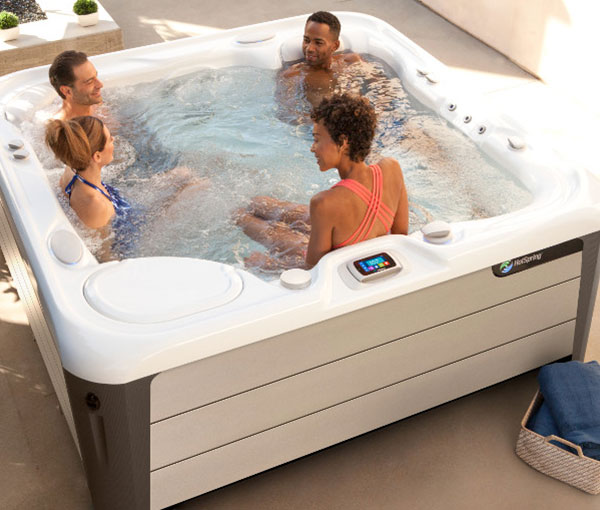 Group of friends in an Aria Hot Tub Spa with Waterfall | Hot Springs Spas available at the Recreational Warehouse Southwest Florida (Naples, Fort Myers and Port Charlotte Locations) Pool Warehouse