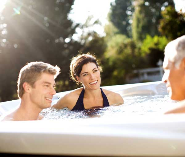Group of friends enjoying their Makena Hot Tub | Caldera Spas available at the Recreational Warehouse Southwest Florida (Naples, Fort Myers and Port Charlotte Locations) Pool Warehouse