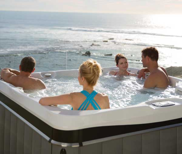 Group of friends enjoying their Tahitian Hot Tub | Caldera Spas available at the Recreational Warehouse Southwest Florida (Naples, Fort Myers and Port Charlotte Locations) Pool Warehouse