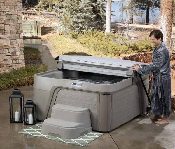 Man unfolding cover on Azure Hot Tub Spa | Freeflow Spas available at the Recreational Warehouse Southwest Florida (Naples, Fort Myers and Port Charlotte Locations) Pool Warehouse
