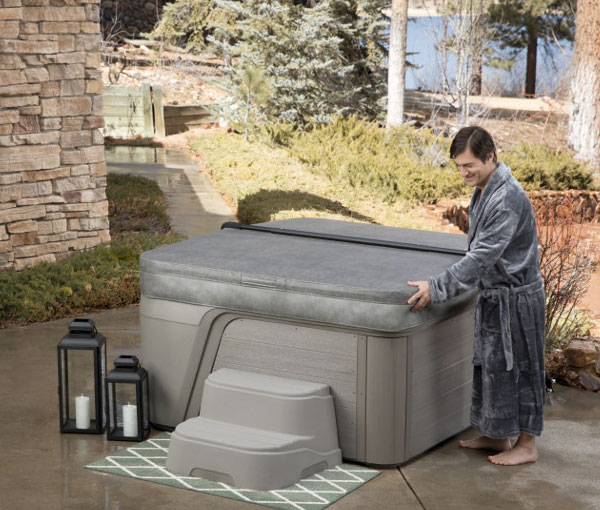 Man placing cover on in Azure Hot Tub Spa | Freeflow Spas available at the Recreational Warehouse Southwest Florida (Naples, Fort Myers and Port Charlotte Locations) Pool Warehouse
