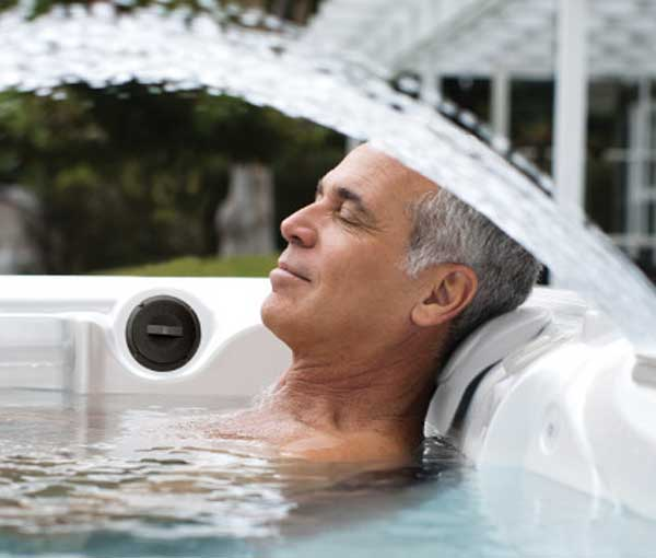 Man relaxing in Makena Hot Tub with Waterfall | Caldera Spas available at the Recreational Warehouse Southwest Florida (Naples, Fort Myers and Port Charlotte Locations) Pool Warehouse
