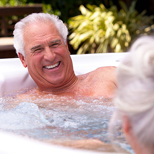Man smiling at wife in a hot tub from The Recreational Warehouse Southwest Florida's Leading Warehouse for Spas, Hot Tubs, Pool Heaters, Pool Supplies, Outdoor Kitchens and more!
