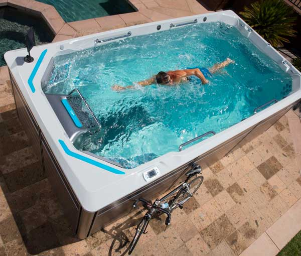 Man swimming in E550 Endless Pool | Endless Pools Fitness Systems available at the Recreational Warehouse Southwest Florida (Naples, Fort Myers and Port Charlotte Locations) Pool Warehouse