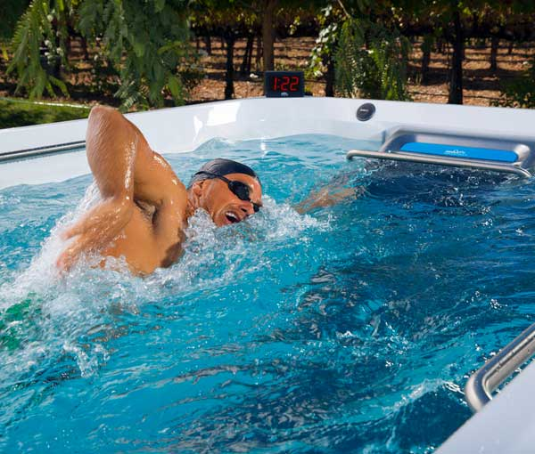 Man swimming in E200 Endless Pool | Endless Pools Fitness Systems available at the Recreational Warehouse Southwest Florida (Naples, Fort Myers and Port Charlotte Locations) Pool Warehouse