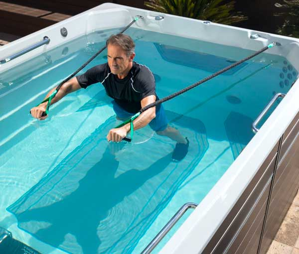Man using resistance ba nds in E550 Endless Pool | Endless Pools Fitness Systems available at the Recreational Warehouse Southwest Florida (Naples, Fort Myers and Port Charlotte Locations) Pool Warehouse