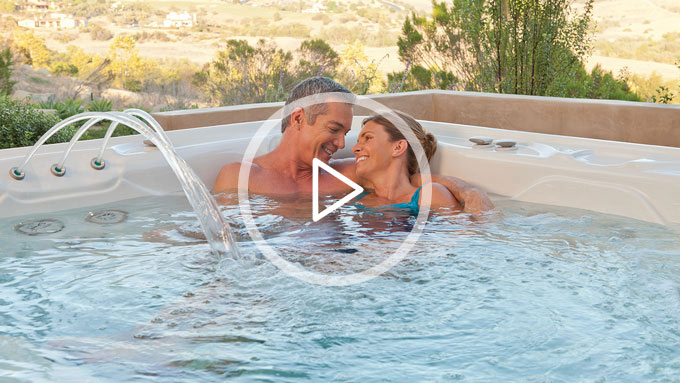 Couple cuddling close and relaxing in a hot tub from The Recreational Warehouse Southwest Florida's Leading Warehouse for Spas, Hot Tubs, Pool Heaters, Pool Supplies, Outdoor Kitchens and more!