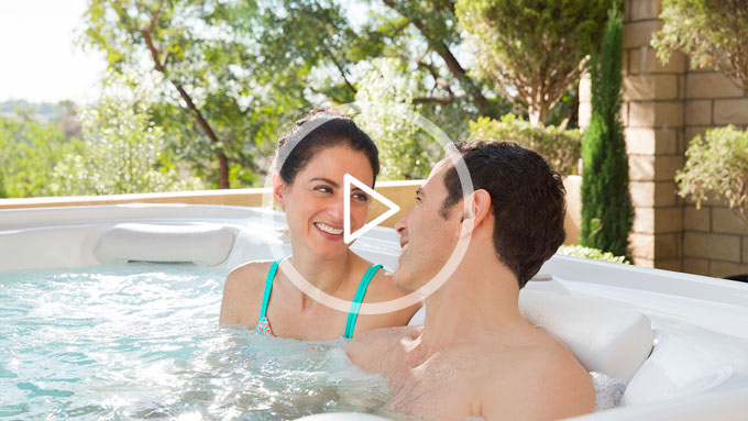 Man and woman adoringly gazing into their eyes in a spa from The Recreational Warehouse Southwest Florida's Leading Warehouse for Spas, Hot Tubs, Pool Heaters, Pool Supplies, Outdoor Kitchens and more!