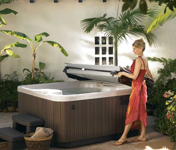 Woman placing cover on SX Hot Tub Spa | Hot Springs Spas available at the Recreational Warehouse Southwest Florida (Naples, Fort Myers and Port Charlotte Locations) Pool Warehouse