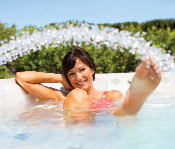 Woman enjoying waterfall in Cantabria Hot Tub Spa | Caldera Spas available at the Recreational Warehouse Southwest Florida (Naples, Fort Myers and Port Charlotte Locations) Pool Warehouse