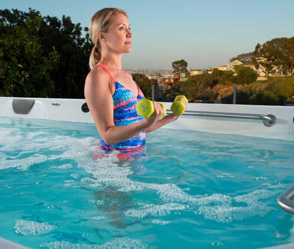 Woman exercising in R200 Endless Pool | Endless Pools Fitness Systems available at the Recreational Warehouse Southwest Florida (Naples, Fort Myers and Port Charlotte Locations) Pool Warehouse