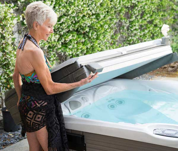 Woman covering her Kauai Caldera Spa | Caldera Spas available at the Recreational Warehouse Southwest Florida (Naples, Fort Myers and Port Charlotte Locations) Pool Warehouse