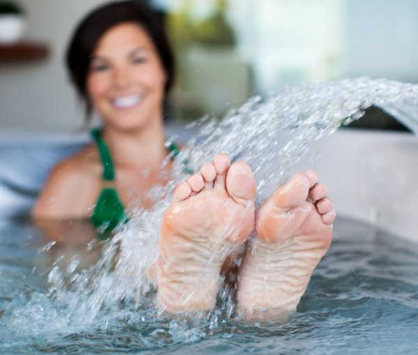 Woman playing in waterfall of Tarino Hot Tub Caldera Spa | Caldera Spas available at the Recreational Warehouse Southwest Florida (Naples, Fort Myers and Port Charlotte Locations) Pool Warehouse