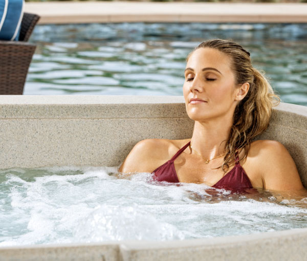 Woman relaxing in Cascina Hot Tub Spa | Freeflow Spas available at the Recreational Warehouse Southwest Florida (Naples, Fort Myers and Port Charlotte Locations) Pool Warehouse