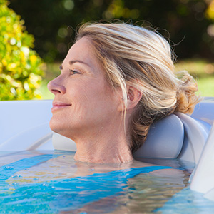 Woman relaxing in a Spa from The Recreational Warehouse Southwest Florida's Leading Warehouse for Spas, Hot Tubs, Pool Heaters, Pool Supplies, Outdoor Kitchens and more!