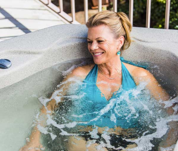 Woman relaxing in Tristar Hot Tub Spa | Freeflow Spas available at the Recreational Warehouse Southwest Florida (Naples, Fort Myers and Port Charlotte Locations) Pool Warehouse