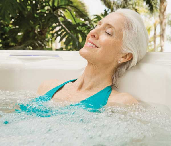 Woman relaxing in Jetsetter Hot Tub Spa | Hot Springs Spas available at the Recreational Warehouse Southwest Florida (Naples, Fort Myers and Port Charlotte Locations) Pool Warehouse