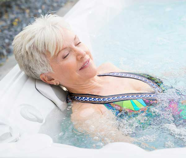 Woman relaxing in Kauai Caldera Spa | Caldera Spas available at the Recreational Warehouse Southwest Florida (Naples, Fort Myers and Port Charlotte Locations) Pool Warehouse