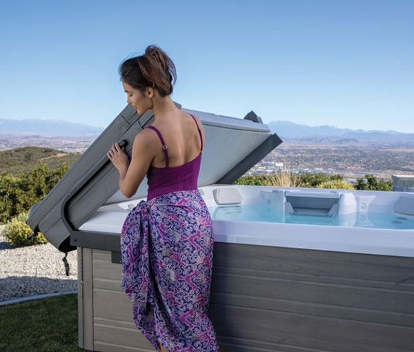 Woman removing cover off Beam Hot Tub Spa | Hot Springs Spas available at the Recreational Warehouse Southwest Florida (Naples, Fort Myers and Port Charlotte Locations) Pool Warehouse