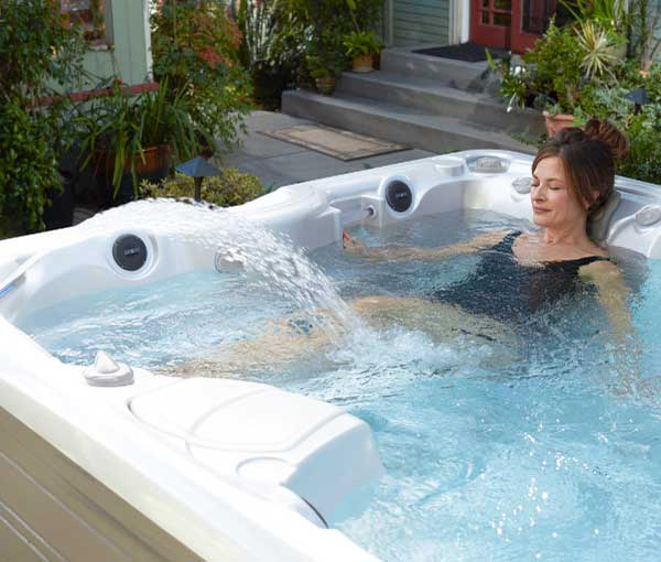 Woman relaxing in lounger of Martinique Hot Tub | Caldera Spas available at the Recreational Warehouse Southwest Florida (Naples, Fort Myers and Port Charlotte Locations) Pool Warehouse