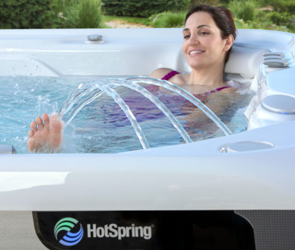 Woman relaxing in Vanguard Hot Tub Spa with Waterfall | Hot Springs Spas available at the Recreational Warehouse Southwest Florida (Naples, Fort Myers and Port Charlotte Locations) Pool Warehouse