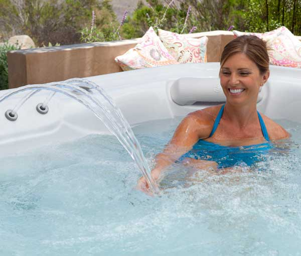 Woman touching waterfall in Grandee Hot Tub Spa | Hot Springs Spas available at the Recreational Warehouse Southwest Florida (Naples, Fort Myers and Port Charlotte Locations) Pool Warehouse