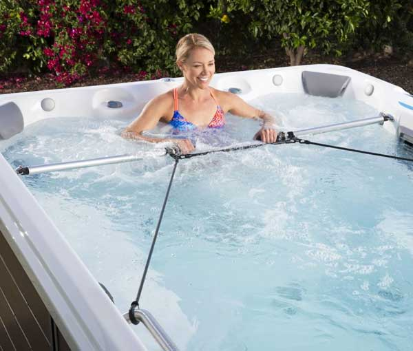 Woman working out in E700 Endless Pool   Endless Pools Fitness Systems available at the Recreational Warehouse Southwest Florida (Naples, Fort Myers and Port Charlotte Locations) Pool Warehouse